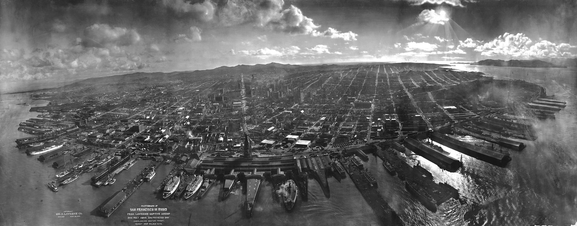 "George R. Lawrence, 1908: ""San Francisco in ruins from Lawrence Captive Airship – 2000 feet [660 m] above San Francisco Bay – Overlooking waterfront. – Sunset over Golden Gate."" Market Street leads directly away from Ferry Building tower, center foreground."